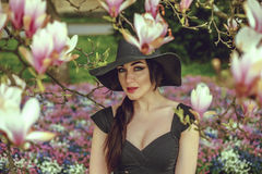 Belle fille avec les cheveux noirs dans une robe noire sur un fond d'une fleur de magnolia Photographie stock