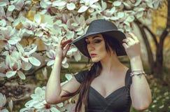 Belle fille avec les cheveux noirs dans une robe noire sur un fond d'une fleur de magnolia Images stock