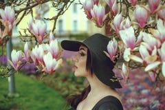 Belle fille avec les cheveux noirs dans une robe noire sur un fond d'une fleur de magnolia Images libres de droits