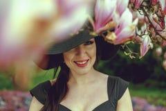 Belle fille avec les cheveux noirs dans une robe noire sur un fond d'une fleur de magnolia Photos libres de droits