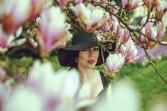 Belle fille avec les cheveux noirs dans une robe noire sur un fond d'une fleur de magnolia Image libre de droits