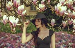 Belle fille avec les cheveux noirs dans une robe noire sur un fond d'une fleur de magnolia Photographie stock libre de droits