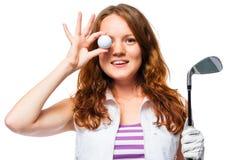 Belle fille avec les cheveux rouges et une boule de golf sur un blanc Photographie stock libre de droits