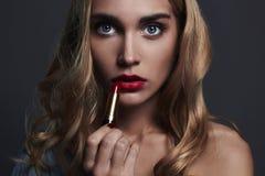 Belle fille avec les languettes rouges jeune femme mettant lipstic rouge Photographie stock libre de droits