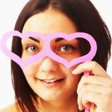 Belle fille avec les verres de papier sous forme de coeurs Photos libres de droits