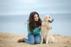 Belle fille avec son chien près de mer Photos stock