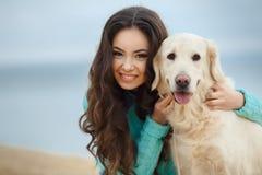 Belle fille avec son chien près de mer Photographie stock libre de droits