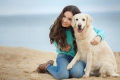 Belle fille avec son chien près de mer Images stock