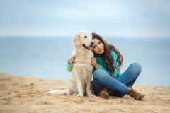 Belle fille avec son chien près de mer Photo stock
