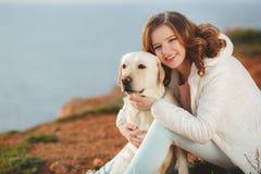 Belle fille avec son chien près de mer Photographie stock
