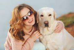 Belle fille avec son chien près de mer Image stock