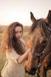 Belle fille avec un cheval dehors Photographie stock libre de droits