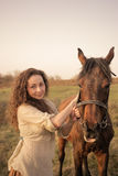 Belle fille avec un cheval dehors Photographie stock