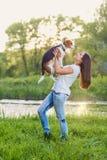 Belle fille avec un chien dans sa main en parc Amitié, h Image stock