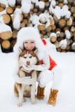 Belle fille avec un chien de traîneau sibérien dans la neige Photos libres de droits