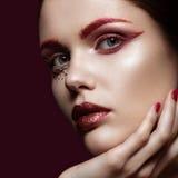 Belle fille avec un maquillage rouge lumineux de mode et cristaux sur le visage Portrait en gros plan Photographie stock