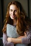 Belle fille avec un oreiller dans des ses mains souriant et regardant in camera Image stock