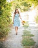 Belle fille avec un panier des fleurs sur une promenade Image stock