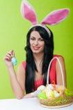 Belle fille avec un panier des oeufs de pâques i Photo stock