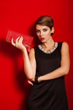Belle fille avec un sac d'embrayage rouge Photo libre de droits
