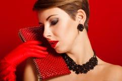 Belle fille avec un sac d'embrayage rouge Images stock