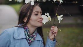Belle fille avec un sourire examine les fleurs blanches de magnolia et les reniffe clips vidéos