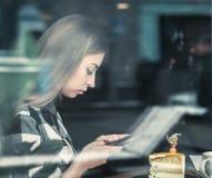 Belle fille avec un téléphone dans un café à la table, Images libres de droits