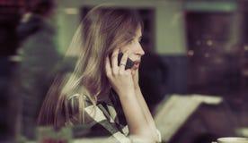 Belle fille avec un téléphone dans un café à la table, Photos stock