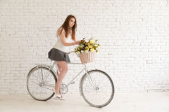 Belle fille avec un vélo et un panier des fleurs Image stock