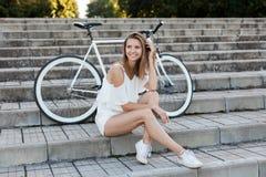 Belle fille avec une bicyclette en parc d'été images stock