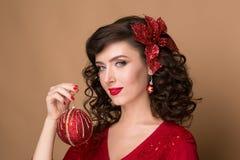 Belle fille avec une boule rouge de Noël Image stock
