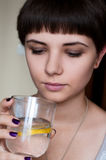 Belle fille avec une coiffure courte regardant l'eau froide avec de la glace et le citron Image stock