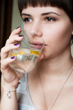 Belle fille avec une coupe de cheveux courte buvant l'eau froide avec de la glace et le citron et des regards dans la distance Images stock