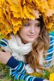 Belle fille avec une guirlande des feuilles sur la tête se trouvant sur Image stock
