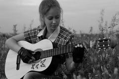 Belle fille avec une guitare Photos stock