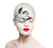 Belle fille avec une photo sur le visage du cupidon. images stock