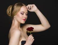 Belle fille avec une rose posant sur un fond sans couture foncé Photographie stock