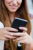 Belle fille ayant l'amusement avec le smartphone après classe Images stock