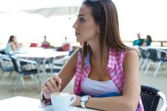 Belle fille ayant le café sur la rue Photos stock