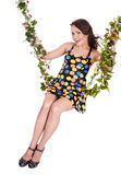 Belle fille balançant sur l'oscillation de fleur. Photographie stock libre de droits
