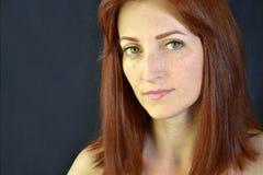 Belle fille blanche avec les cheveux rouges et les yeux verts avec des prolongements de cil sur le fond foncé regardant en avant photos libres de droits