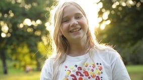 Belle fille blonde adolescente de sourire contre le vert du parc d'été Peu d'enfant ayant beaucoup d'amusement passant le temps banque de vidéos