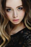 Belle fille blonde avec de grands yeux bleus sur le fond noir Photographie stock libre de droits