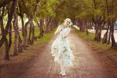 Belle fille blonde avec des arbres, robe blanche Photo libre de droits