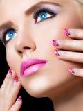 Belle fille blonde avec les lèvres et les clous roses photographie stock libre de droits