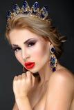 Belle fille blonde avec une couronne d'or, des boucles d'oreille et le professi Image stock