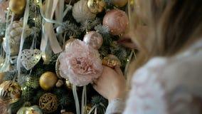 Belle fille blonde dans des pyjamas décorant l'arbre de Noël banque de vidéos