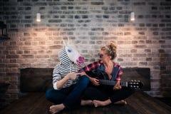 Belle fille blonde dans des vêtements causaux jouant la musique sur la guitare pour l'homme bizarre Image stock