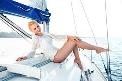 Belle fille blonde dans la bonne forme avec les lèvres rouges de longs cheveux foncés et de peau bronzage dans l'allocation des p Image stock