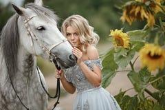 Belle fille blonde dans la robe grise étreignant un cheval sur la nature dedans photo stock